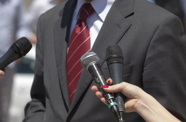 Journalists making interview with businessperson or politician